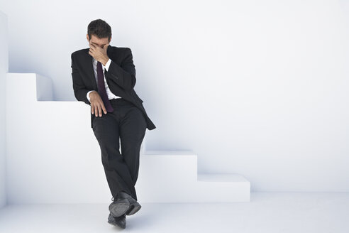 Businessman in black suit sitting on stairs with head in hand - PDYF000409