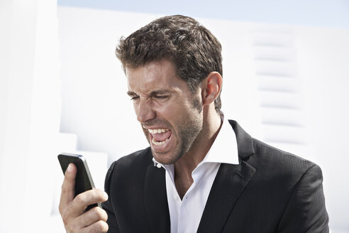 Businessman in black suit shouting in mobile phone - PDYF000431