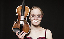 Portrait of teenage girl holding violin, close up - DISF000005