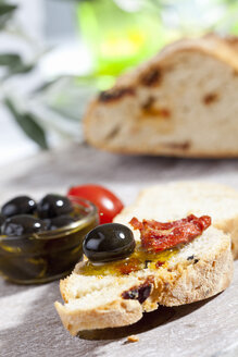 Slice of bread with olive and dried tomato, close up - CSF017745
