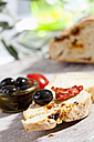Slice of bread with olive and dried tomato, close up - CSF017748