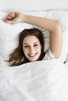Portrait of young woman lying on bed, smiling - SPOF000071