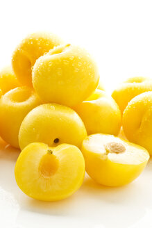 Yellow plums on white background, close up - MAEF006104