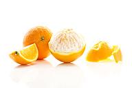 Peeled and whole oranges on white background, close up - MAEF006113
