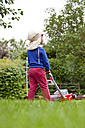 Germany, Girl driving toy lawn mower in garden - JFEF000037
