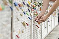 Germany, Bavaria, Munich, Man locking love lock - CRF002334