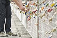 Germany, Bavaria, Munich, Man locking love lock - CR002335