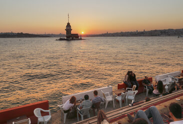 Turkey, Istanbul, People sitting in cafe at Bosphorus and Maidens Tower in background - SIE003493