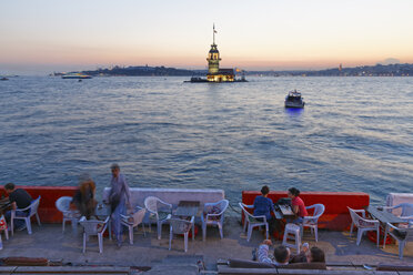 Turkey, Istanbul, People sitting in cafe in Bosphorus, Maidens Tower in background - SIE003496