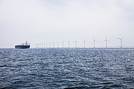 Germany, Hamburg, View of cargo ship in front of the wind-wheels of an offshore windpark - DIS000042