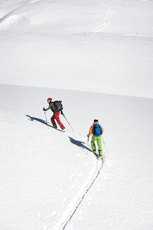 Austria, Men skiing on mountain at Salzburger Land - RN001172