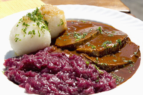 Plate of sauerbraten marinated beef with red cabbage and potato dumpling - CSF017821