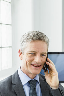Germany, Businessman talking on mobile phone, smiling - SPO000135