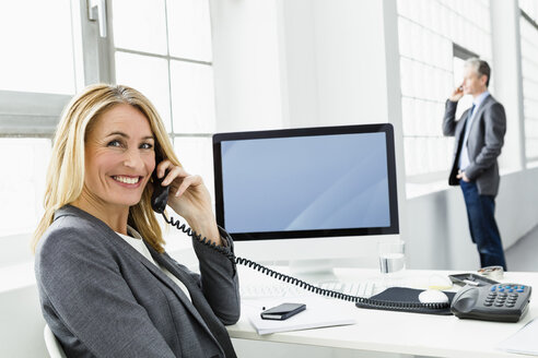Germany, Businesswoman talking on telephone while man in background - SPO000153