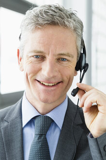 Germany, Businessman talking on head phone, smiling - SPO000156