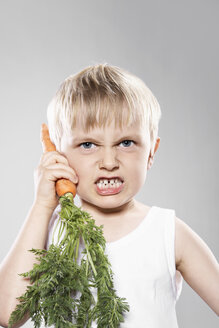 Boy imitating carrot as telephone, close up - PD000312