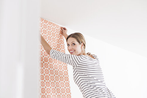 Woman sticking wallpaper on wall, smiling - FMKF000630