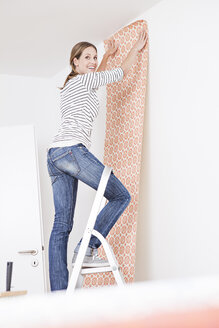 Woman sticking wallpaper on wall - FMKF000633