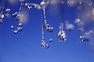 Splashing water against blue background - JTF000314