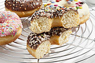 Variety of doughnuts topped with icing and sprinkles on cooling rack - CSF017936