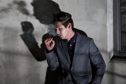 Germany, Bavaria, Young man smoking in dark corner - MAE006280