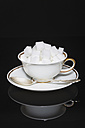 Cup of sugar cubes with saucer and spoon on black background - MU001306