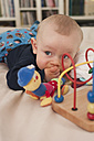 Germany, Hesse, Frankfurt, Baby boy playing with toy - MUF001289