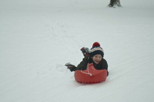 Germany, Baden Wuerttemberg, Constance, Boy skidding in snow, smiling - JED000017