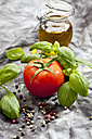 Vine tomato with basil herb ,colorful peppercorns and glass with olive oil on grey background, close up - CSF018097