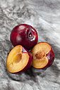 Red plums on grey background, close up - CSF018231