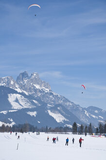 Austria, Tourists are skiing and paraglider flying at Tannheim Alps - UM000615