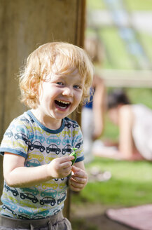 Austria, Portrait of boy holding balloon and laughing, close up - LF000509