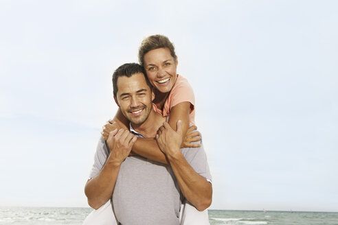 Spain, Mid adult man giving piggy back ride to woman, smiling - SKF001221