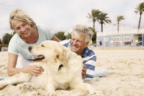Spain, Senior couple with dog on beach at Palma de Mallorca, smiling - SKF001236