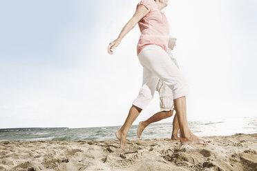 Spain, Senior couple walking on beach at Palma de Mallorca - SKF001182