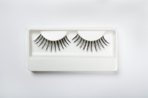 Fake eyelashes in plastic container on white background - TDF000028