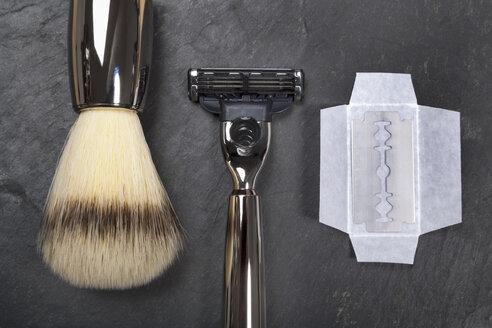 Shaving brush, razor and razor blade on slate board, close up - TDF000024