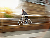 Germany, Cologne, Mature man riding bicycle - RHYF000361