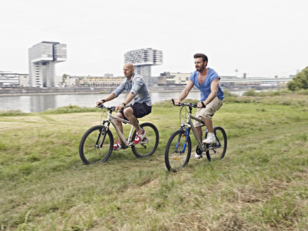 Germany, Cologne, Men riding bicycle - RHYF000364