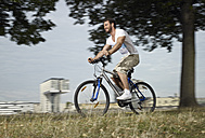 Germany, Cologne, Young man riding bicycle - RHYF000367