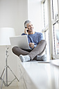 Germany, Bavaria, Munich, Mature man talking on mobile and using laptop, smiling - RBF001311