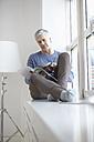 Germany, Bavaria, Munich, Mature sitting at window and reading magazine - RBF001308