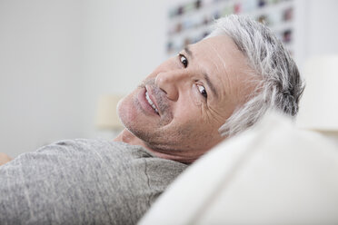 Germany, Bavaria, Munich, Portrait of mature man sitting on couch, smiling - RBF001235