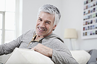 Germany, Bavaria, Munich, Portrait of mature man sitting on couch, smiling - RBF001248