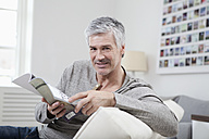 Germany, Bavaria, Munich, Portrait of mature man reading magazine on couch, smiling - RBF001266