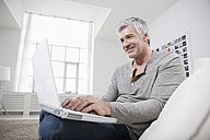 Germany, Bavaria, Munich, Mature man using laptop on couch, smiling - RBF001270