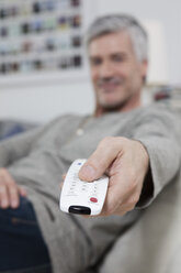Germany, Bavaria, Munich, Mature man changing channels with remote control - RBF001209