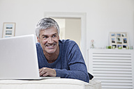 Germany, Bavaria, Munich, Mature man using laptop on couch, smiling - RBF001273