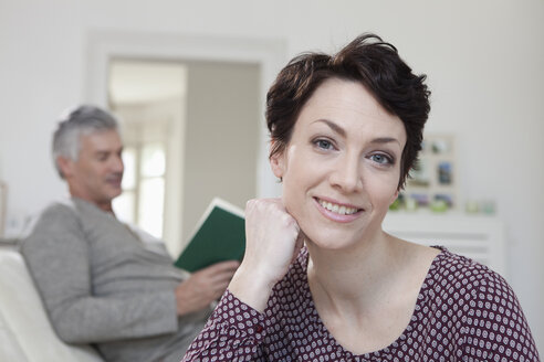 Germany, Bavaria, Munich, Portrait of woman smiling while man reading book in background - RBF001231