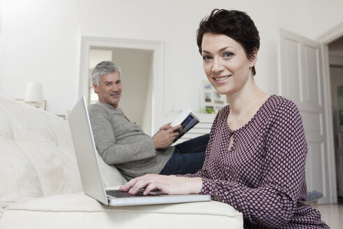 Germany, Bavaria, Munich, Woman using laptop while man reading book in background - RBF001265